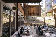 """Patrons eat on the patio at Bartaco in Arlington, Va., on Thursday, Sept. 2, 2021. The restaurant uses an automated app for ordering and payments, accessed via a barcode attached to the table, and instead of servers they use """"food runners"""" to get the orders to the tables. (AP Photo/Jacquelyn Martin)"""
