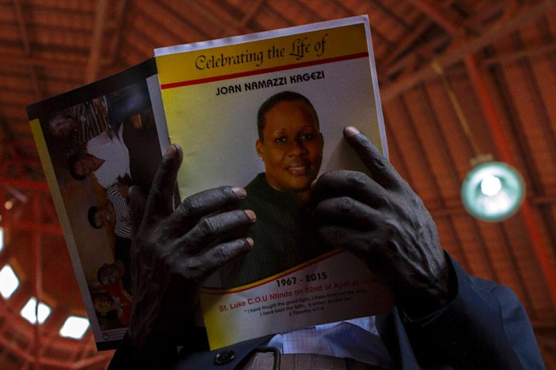 A man holds a programme at a memorial service for late acting assistant director of public prosecution Joan Kagezi, on April 2, 2015 in Kampala