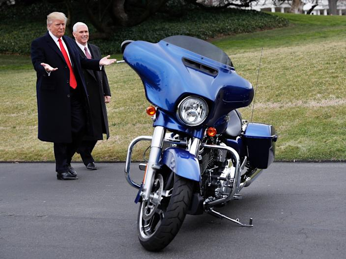 President Donald Trump and Vice President Mike Pence are pictured with a Harley-Davidson motorcycle.