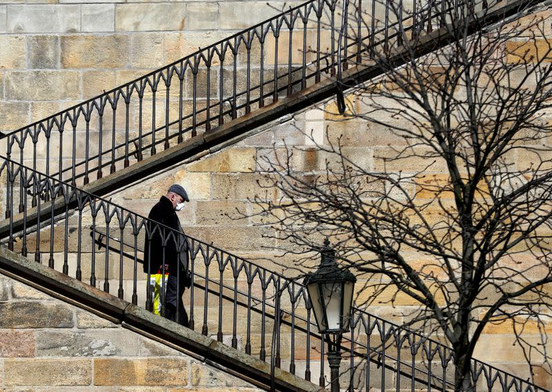 A man wearing a face mask walks down the stairs in Prague