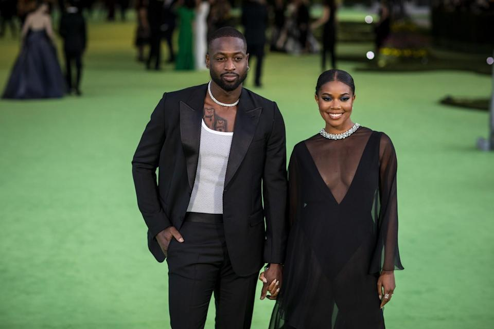 A man in a black suit and a woman in a black dress posing on a green carpet