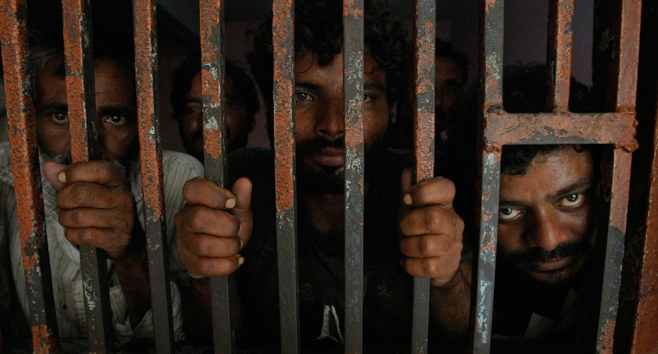 <p>Arrested Indian fishermen look out at a lock up at a police station in Karachi, Pakistan, Thursday, April 27, 2017. Pakistan's Maritime Security Agency (MSA) has arrested 29 Indian fishermen along with confiscating five fishing boats from the Arabian Sea for violating its territorial waters, a Pakistani police officer said. (AP Photo/Fareed Khan) </p>