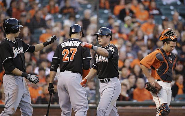 Miami Marlins' Derek Dietrich, second from right, is greeted by teammate Christian Yelich, left, after hitting a home run off San Francisco Giants starting pitcher Yusmeiro Petit in the third inning of a baseball game Friday, May 16, 2014, in San Francisco. In the background are Marlins' Giancarlo Stanton (27) and Giants catcher Buster Posey, right. (AP Photo/Eric Risberg)