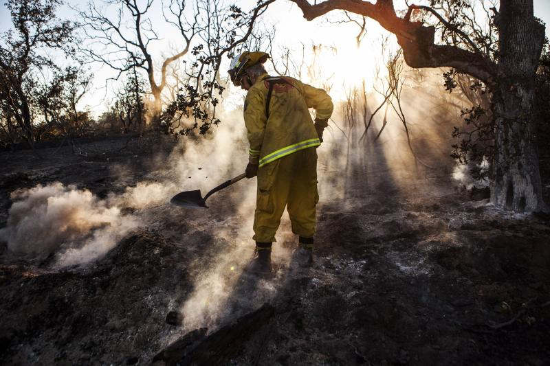Shasta County firefighter Bob Baker mops up an area affected by the Clover Fire in Happy Valley