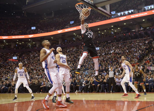 Toronto Raptors guard Norman Powell (24) slam dunks the ball past Philadelphia 76ers center Al Horford (42) and guard Ben Simmons (25) during the first half of an NBA basketball game, Wednesday, Jan. 22, 2020 in Toronto. (Nathan Denette/The Canadian Press via AP)