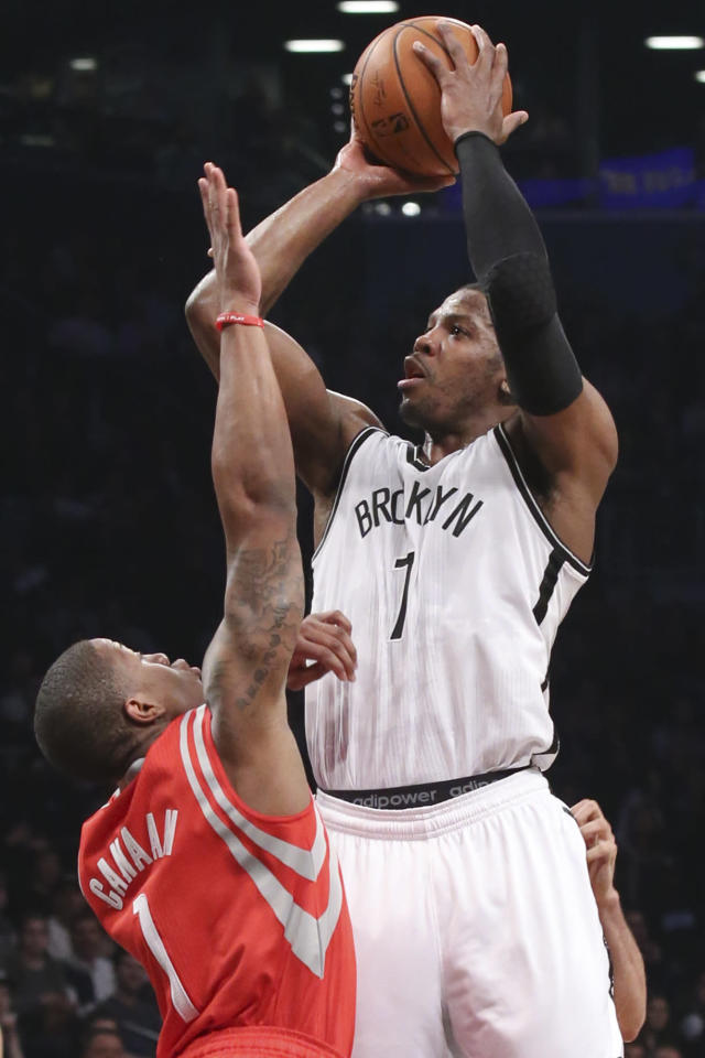 Brooklyn Nets guard Joe Johnson (7) shoots over Houston Rockets guard Isaiah Canaan (1) during the first half of their NBA basketball game at the Barclays Center, Tuesday, April 1, 2014, in New York. (AP Photo/John Minchillo)