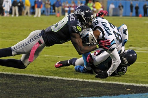 Carolina Panthers' Louis Murphy (83) is stopped short of the end zone by Seattle Seahawks' Brandon Browner (39) and Marcus Trufant (23) during the fourth quarter of an NFL football game in Charlotte, N.C., Sunday, Oct. 7, 2012. The Seahawks won 16-12. (AP Photo/Bob Leverone)