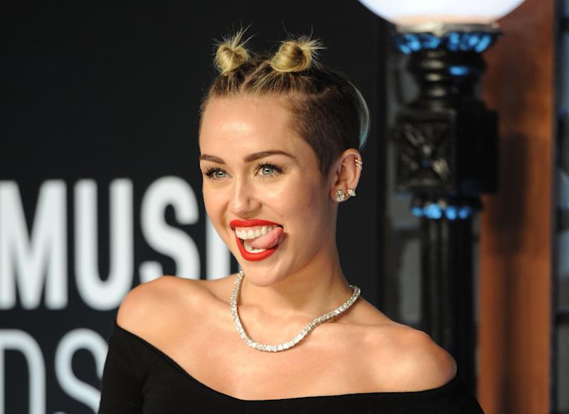 """FILE - This Aug. 25, 2013 file photo shows singer Miley Cyrus at the MTV Video Music Awards in the Brooklyn borough of New York. Cyrus says in an interview clip that she doesn't listen to the negative comments regarding her performance on the MTV Video Music Awards. The pop star says she felt she and Robin Thicke were making history with the risque performance of their hits """"We Can't Stop"""" and """"Blurred Lines."""" The comments were Cyrus' first since the Aug. 25 show. The clip was recorded last week and posted Tuesday morning on MTV's website. Cyrus compares the performance to that of Madonna and Britney Spears, who once kissed on air. (Photo by Evan Agostini/Invision/AP, File)"""