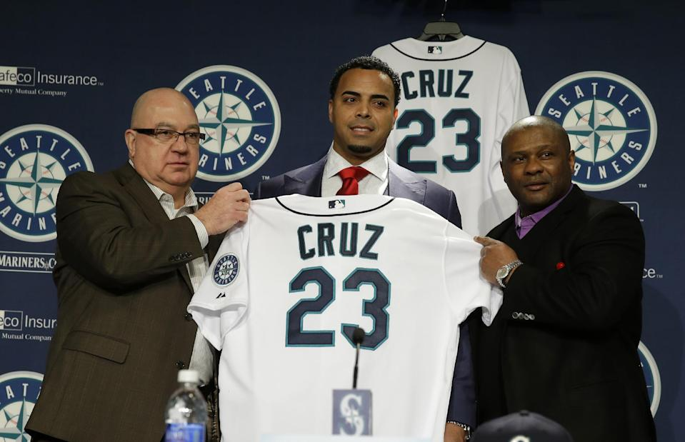Seattle Mariners' Nelson Cruz, center, displays his new jersey after he was officially introduced by manager Lloyd McClendon, right, and general manager Jack Zduriencik, left, during a baseball news conference, Thursday, Dec. 4, 2014, in Seattle. (AP Photo/Ted S. Warren)