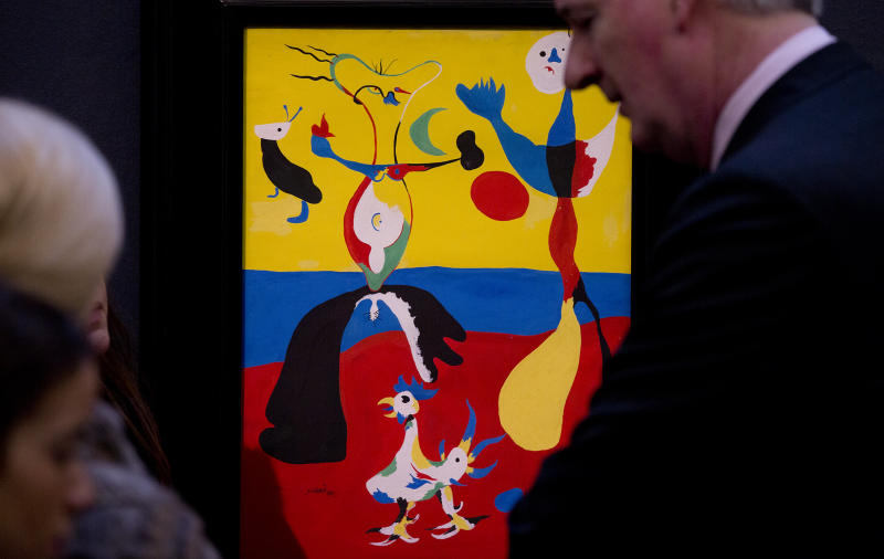"""Visitors look at a work by Joan Miro entitled """"Le Fermier et son epouse"""" 1936, at Sotheby's auction house during a press preview in London, Thursday, Jan. 31, 2013. The work is estimated to sell for some 5.5-7.5 million pounds ( US$ 8.7-11.867 million, euro 6.421-8.752 million) when sold at auction on Feb. 5 in London. (AP Photo/Alastair Grant)"""