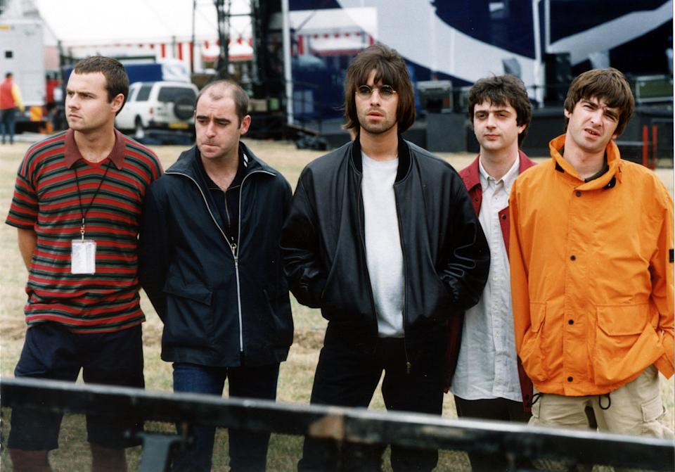 """7th MAY : On this day in 1995 rock group Oasis were top of the charts with their first number one, 'Some might Say'. The band Oasis line up before their Knebworth Park concert. (l-r) drummer Alan White, rhythm guitarist Paul """"Bonehead"""" Arthurs, lead singer Liam Gallagher, bass player Paul """"Guigsy"""" McGuigan and guitarist and songwriter Noel Gallagher.  * 25/8/99 :  The band have revealed that their bass player Paul 'Guigsy'  McGuigan (second right) is to leave the band.  Only two weeks after it was revealed that guitarist, Bonehead (second left) was leaving.   (Photo by Stefan Rousseau - PA Images/PA Images via Getty Images)"""
