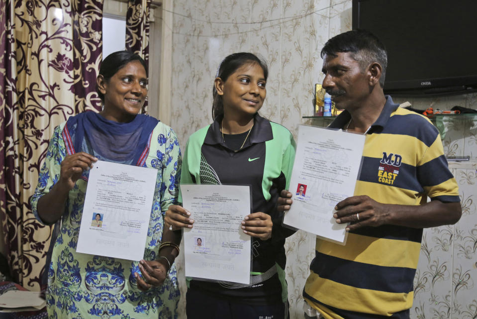 Radhika Gill, center, with her father Bhittu Gill and mother Shaloo Gill display their domicile certificates in Jammu, India, July 30, 2020. A year after India ended disputed Kashmir's semi-autonomous status and downgraded it to a federally governed territory, authorities have begun issuing residency and land ownership rights to outsiders for the first time in almost a century. Documents accessed and reviewed by The Associated Press show at least 60,000 have gained residency in the last two months including Hindu refugees, Gurkha soldiers and bureaucrats. (AP Photo/Channi Anand)