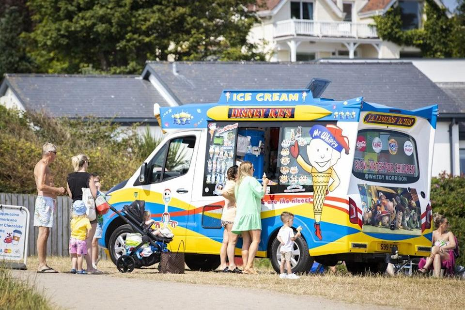 People buy an ice cream at Helen's Bay beach in County Down, Northern Ireland (Liam McBurney/PA) (PA Wire)