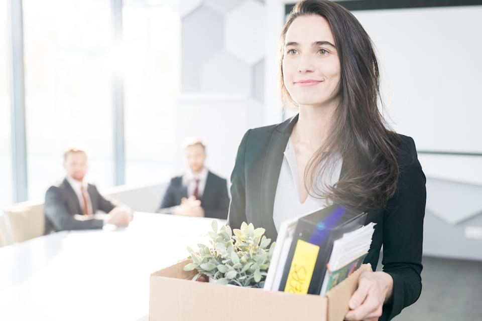 A woman leaving an office carrying her possessions after resigning