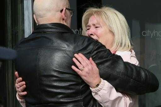 Linda Nash (R), who lost her brother William on Bloody Sunday, is comforted outside the City Hotel in Derry