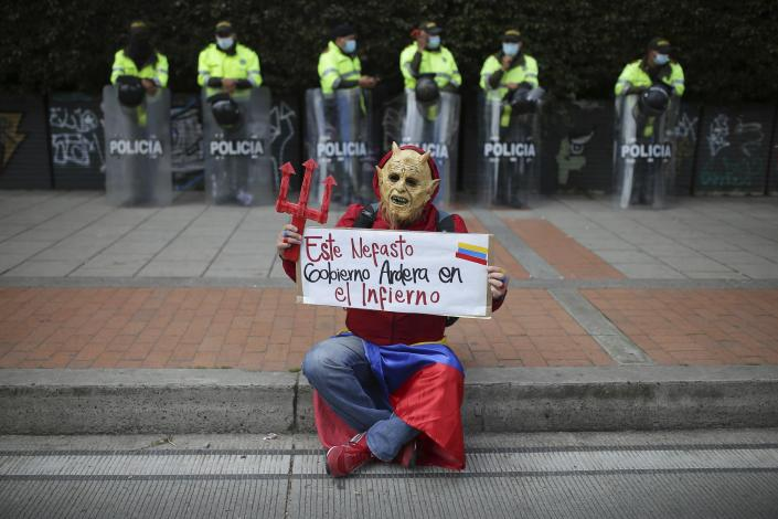 """A man in a devil costume holds the Spanish sign """"This disastrous government will burn in hell"""" in front of police standing on the sidelines of an anti-government march in Bogota, Colombia, Wednesday, May 19, 2021. Colombians have taken to the streets for weeks across the country after the government proposed tax increases on public services, fuel, wages and pensions. (AP Photo/Ivan Valencia)"""