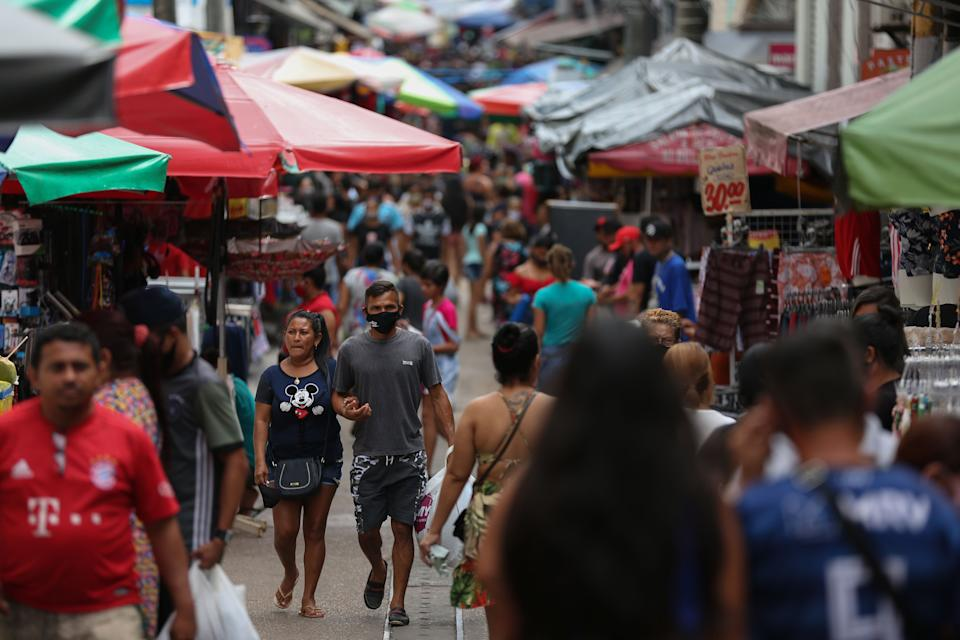 """People walk along Manaus city center, Amazonas state, Brazil, on September 25, 2020. - The Brazilian city of Manaus, which was devastated by the coronavirus pandemic, may have suffered so many infections that its population now benefits from """"herd immunity,"""" according to a preliminary study. Published on the website medRxiv, the study analyzed infection data with mathematical modeling to estimate that 66 percent of the population had antibodies to the new coronavirus in Manaus, where the pandemic's passage was as fast as it was brutal. (Photo by MICHAEL DANTAS / AFP) (Photo by MICHAEL DANTAS/AFP via Getty Images)"""
