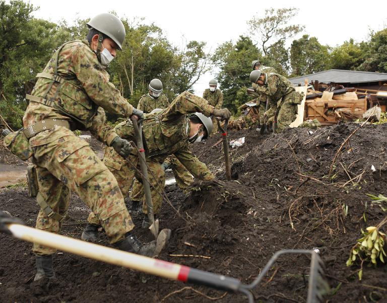 Members of Japan's Ground Self-Defense Force search for missing people on October 21, 2013 after a landslide caused by heavy rains from Typhoon Wipha lashed Oshima island