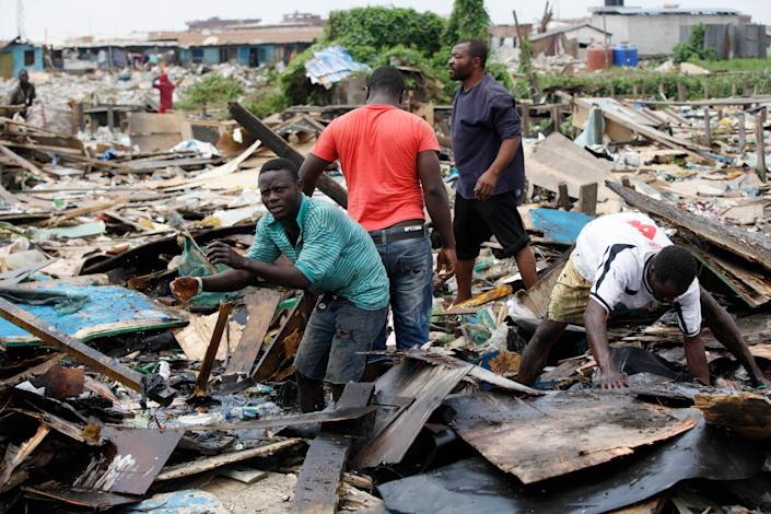 In this image taken Thursday Feb. 28, 2013 residents salvage wood from demolished houses at Ijora Badia slum in Lagos, Nigeria. The bulldozers arrived at dawn to this neighborhood of shanty homes and concrete buildings in Nigeria's largest city, followed by police officers in riot gear carrying Kalashnikov assault rifles. The police banged on doors, corralling the thousands who live in Ijora-Badia off to the side as the bulldozers' blades tore through scrap-lumber walls, its track grinding the possessions inside into the black murk of swamp beneath it. It left behind only a field of debris that children days later picked through, their small hands dodging exposed rusty nails to pull away anything of value left behind. (AP Photo/Sunday Alamba)