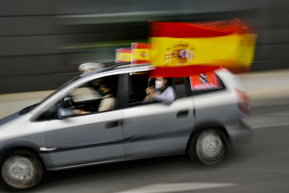People wave Spanish flags during a drive-in protest organised by Spain's far-right Vox party against the Spanish government's handling of the nation's coronavirus outbreak, in Pamplona, northern Spain, Saturday, May 23, 2020. (AP Photo/Alvaro Barrientos)