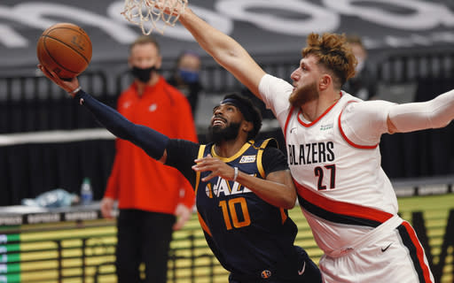 Utah Jazz guard Mike Conley, left, shoots as Portland Trail Blazers center Jusuf Nurkic defends during the first half of an NBA basketball game in Portland, Ore., Wednesday, Dec. 23, 2020. (AP Photo/Steve Dipaola)