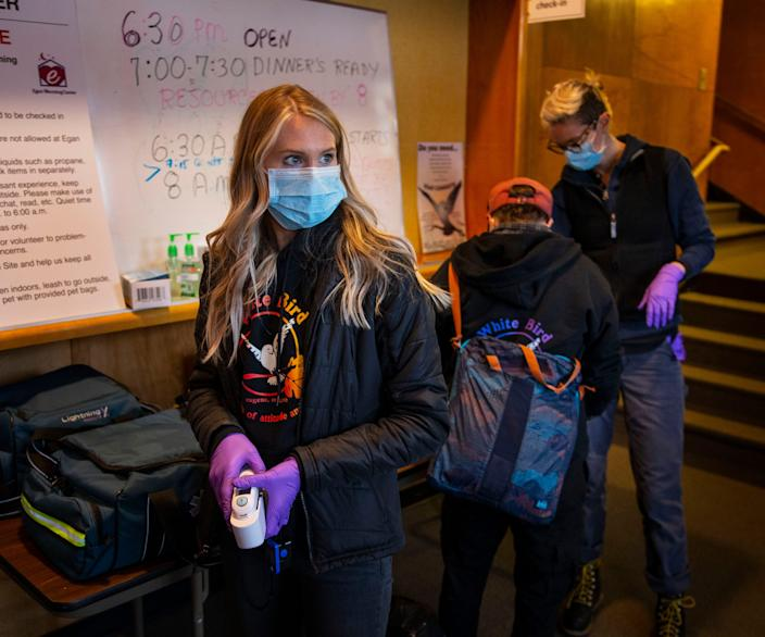 Certified Nursing Assistant Celene Eldrich, left, a volunteer for CAHOOTS waits to screen guests for health concerns at the Egan Warming Center's Springfield, Ore.