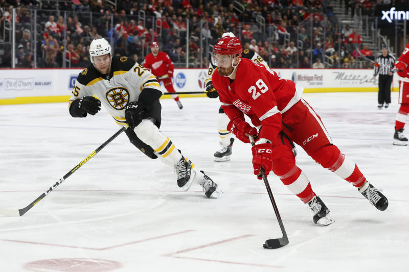 Detroit Red Wings left wing Brendan Perlini (29) shoots as Boston Bruins defenseman Brandon Carlo (25) defends in the second period of an NHL hockey game Sunday, Feb. 9, 2020, in Detroit. Perlini scored on the shot. (AP Photo/Paul Sancya)