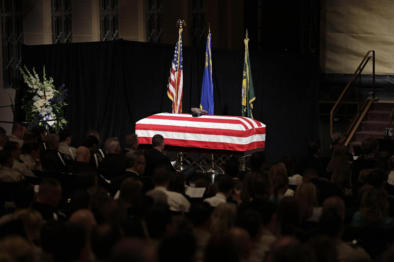 A flag covers the casket of Las Vegas Metropolitan Police Officer Alyn Beck during his memorial service at The Smith Center for the Performing Arts Saturday, June 14, 2014 in Las Vegas. Two suspects shot and killed Beck, 41, and fellow police officer Igor Soldo, 31, in an ambush at a Las Vegas restaurant Sunday, June 8, 2014, before fatally shooting a third person inside a nearby Wal-Mart, authorities said. (AP Photo/John Locher, Pool)