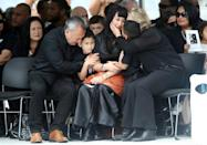 Widow of late New Zealand All Blacks rugby legend Jonah Lomu, Nadene Lomu (C) is comforted by her two sons, Brayley (C-L) and Dhyreille (C-R), her mother Lois Kuiek and father Mervyn Kuiek during memorial service on November 30, 2015