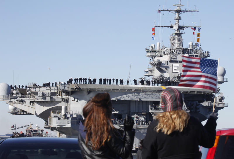 Kimberly Yurtsever of Norfolk waves an American flag as she and her daughter, Janice Bradley, bid goodbye as the nuclear powered aircraft carrier USS Enterprise deploys to support forces in Afghanistan at Naval Station Norfolk in Norfolk, Va., Thursday, Jan. 13, 2011. The USS Enterprise is deploying without its former commander as Navy brass investigates bawdy, sexually themed videos he showed to thousands of crew members. (AP Photo/Steve Helber)