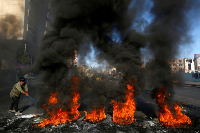A man burns tires during ongoing anti-government protests in Najaf