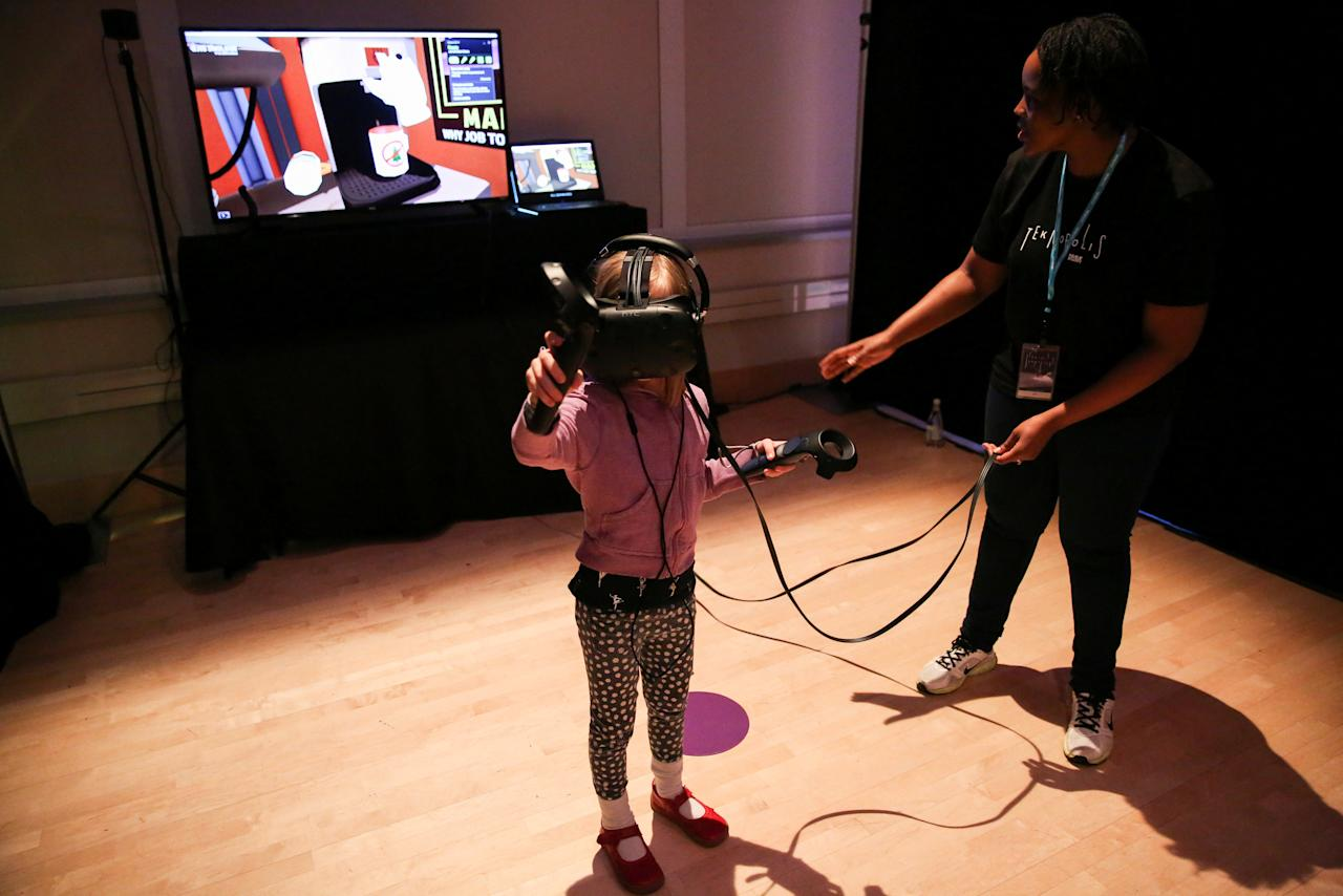 "Cecelia Johnston, 7, interacts in the virtual reality ""Job Simulator,"" virtual reality simulation video game created by Owlchemy Labs, at Teknopolis, a participatory arts-tech exhibit at the Brooklyn Academy of Music (BAM) in Brooklyn, New York, U.S., February 25, 2017.   REUTERS/Ashlee Espinal"