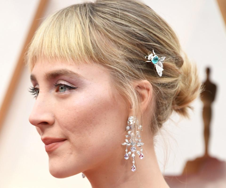 """Adir Abergel put our plastic '90s butterfly clips to shame when he added this modern Gucci accent to Saoirse Ronan's bun (complete with <a href=""""https://www.refinery29.com/en-us/2020/02/9384777/saoirse-ronan-bangs-haircut-oscars-2020"""" rel=""""nofollow noopener"""" target=""""_blank"""" data-ylk=""""slk:brand-new baby bangs"""" class=""""link rapid-noclick-resp"""">brand-new baby bangs</a>).<span class=""""copyright"""">Photo: Steve Granitz/WireImage.</span>"""