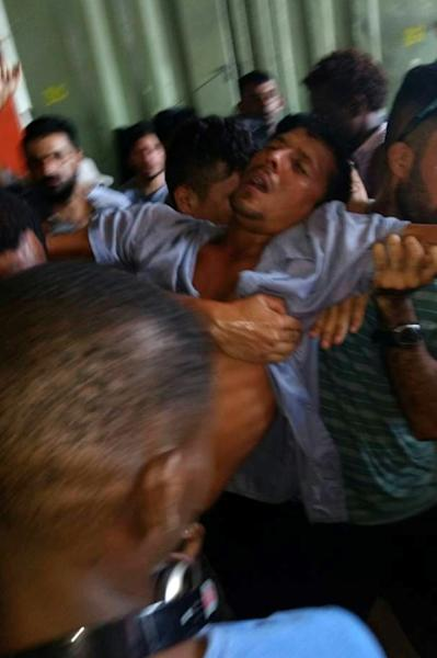 This handout photo taken by Abdul, a refugee on Manus, shows a man being helped after collapsing from stress as asylum-seekers refuse to leave the Manus Island regional refugee processing centre