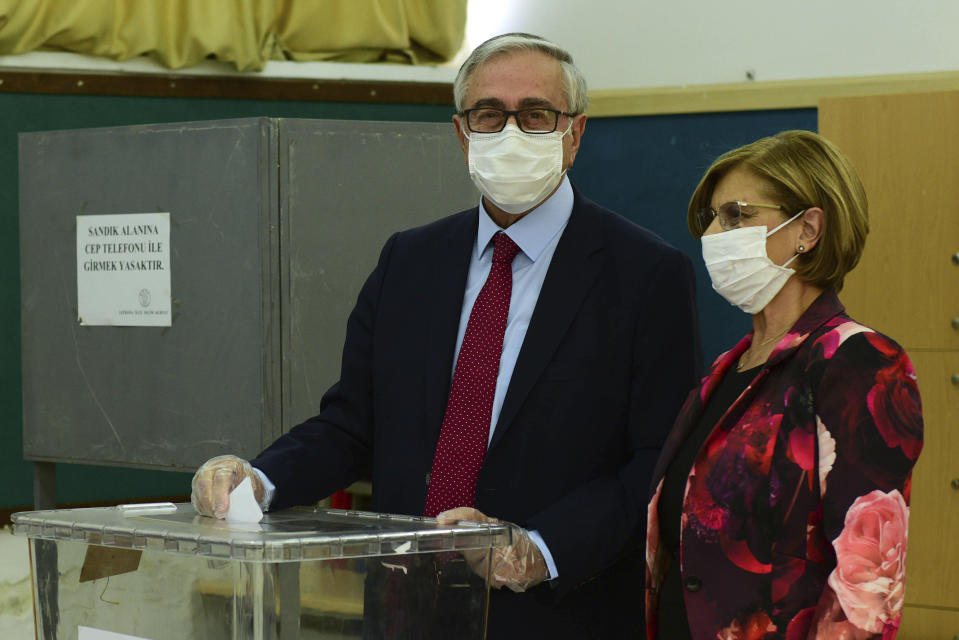 Turkish Cypriot leader and candidate Mustafa Akinci and his wife Merak Akinci cast their ballots at a polling station in the Turkish occupied area in the north part of the divided capital Nicosia, Cyprus, Sunday, Oct. 18, 2020. Turkish Cypriots are voting in a leadership runoff to chose between an incumbent who pledges a course less bound by Turkey's dictates and a challenger who favors even closer ties to Ankara. (AP Photo/Nedim Enginsoy)