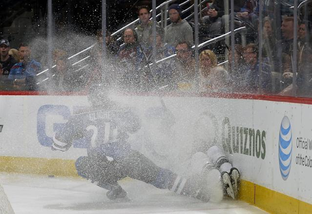Colorado Avalanche right wing Marc-Andre Cliche (24) drives a Minnesota Wild player into the boards in a spray of ice during the first period of an NHL hockey game on Saturday, Nov. 30, 2013, in Denver. (AP Photo/Jack Dempsey)