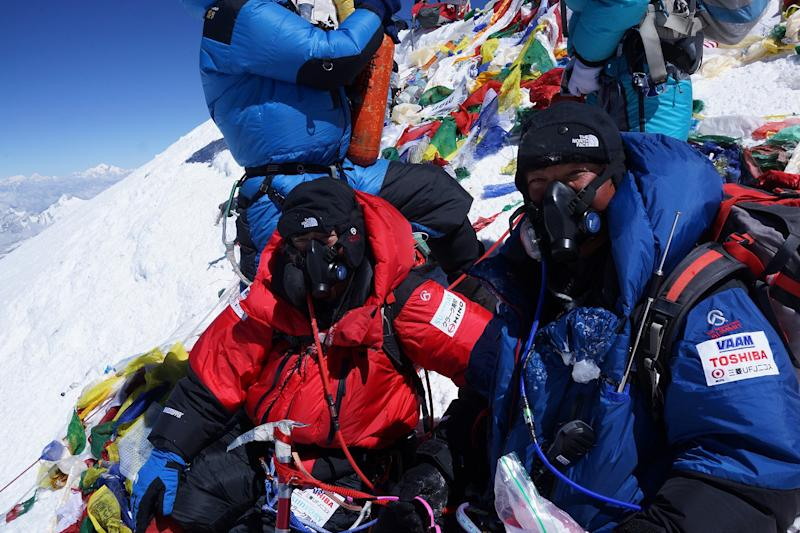 In this photo distributed by MIURA DOLPHINS CO., LTD., 80-year-old Japanese extreme skier Yuichiro Miura, left, who has had four heart operations in recent years, and his son, Gota, are atop the summit of Mount Everest as he becomes the oldest person to climb the world's tallest mountain Thursday, May 23, 2013. Miura, who also conquered the 29,035-foot (8,850-meter) peak when he was 70 and 75, reached the summit at 9:05 a.m. local time, according to a Nepalese mountaineering official and Miura's Tokyo-based support team. (AP Photo/MIURA DOLPHINS CO., LTD.) MANDATORY CREDIT