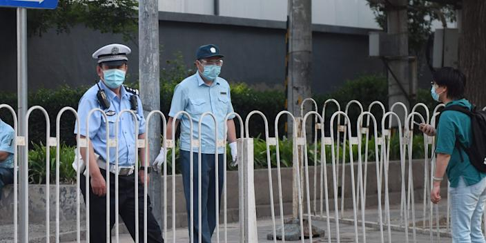 A policeman stands guard behind a barrier blocking the entrance to a closed off residential compound near the closed Xinfadi market in Beijing on June 13, 2020. - The huge wholesale market has become the centre of focus for a new cluster of coronavirus cases in Beijing, where nervous local officials have begun mass testing, closing schools and neighbourhoods, and turned sharp scrutiny towards the food supply chain. (Photo by GREG BAKER / AFP) (Photo by GREG BAKER/AFP via Getty Images)