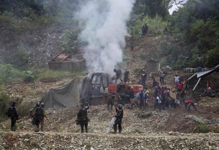 """Gold miners try to put out a fire on machinery set by National Police, bottom, as soldiers stand guard on the periphery at an illegal mining operation, as part of the Armed Forces' """"Operation Guamuez III"""" in Magui Payan, Colombia, Tuesday, April 20, 2021. None of the workers were detained during the destruction of machinery, but in previous days some machinists and material suppliers were detained, according to Army Col. Pedro Pablo Astaiza. (AP Photo/Fernando Vergara)"""