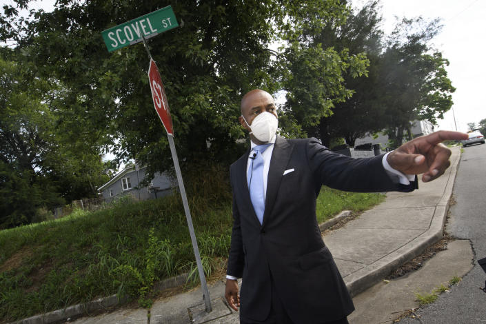 Tennessee State Rep. Harold Love, Jr. points toward interstate I-40 as he walks down his family's former street on the north side Monday, July, 19, 2021, in Nashville, Tenn. Love Jr.'s father, a Nashville city councilman, was forced to sell his family home here to make way for the highway, but put up a fight in the 1960s against the rerouting of Interstate 40 because he believed it would stifle and isolate Nashville's Black community. Love Jr. is now part of a group pushing to build a cap across the highway that creates a community space to help reunify the city. (AP Photo/John Amis)