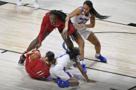 Louisville's Norika Konno, bottom left, and Olivia Cochran, top left, keep the ball from DePaul's Maya Stovall, bottom right, and Kayla Caudle, top right, during the first half of an NCAA college basketball game Friday, Dec. 4, 2020, in Uncasville, Conn. (AP Photo/Jessica Hill)