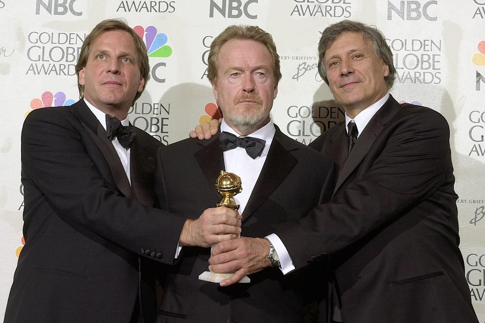"""Producers Doug Wick(L) and David Franzoni(R) join director Ridley Scott(C) after their film """"Gladiator"""" was awarded Best Motion Picture- Drama during the 58th Annual Golden Globes in Beverly Hills, California 21 January 2001. AFP PHOTO Lucy NICHOLSON        (Photo credit should read LUCY NICHOLSON/AFP/GettyImages)"""