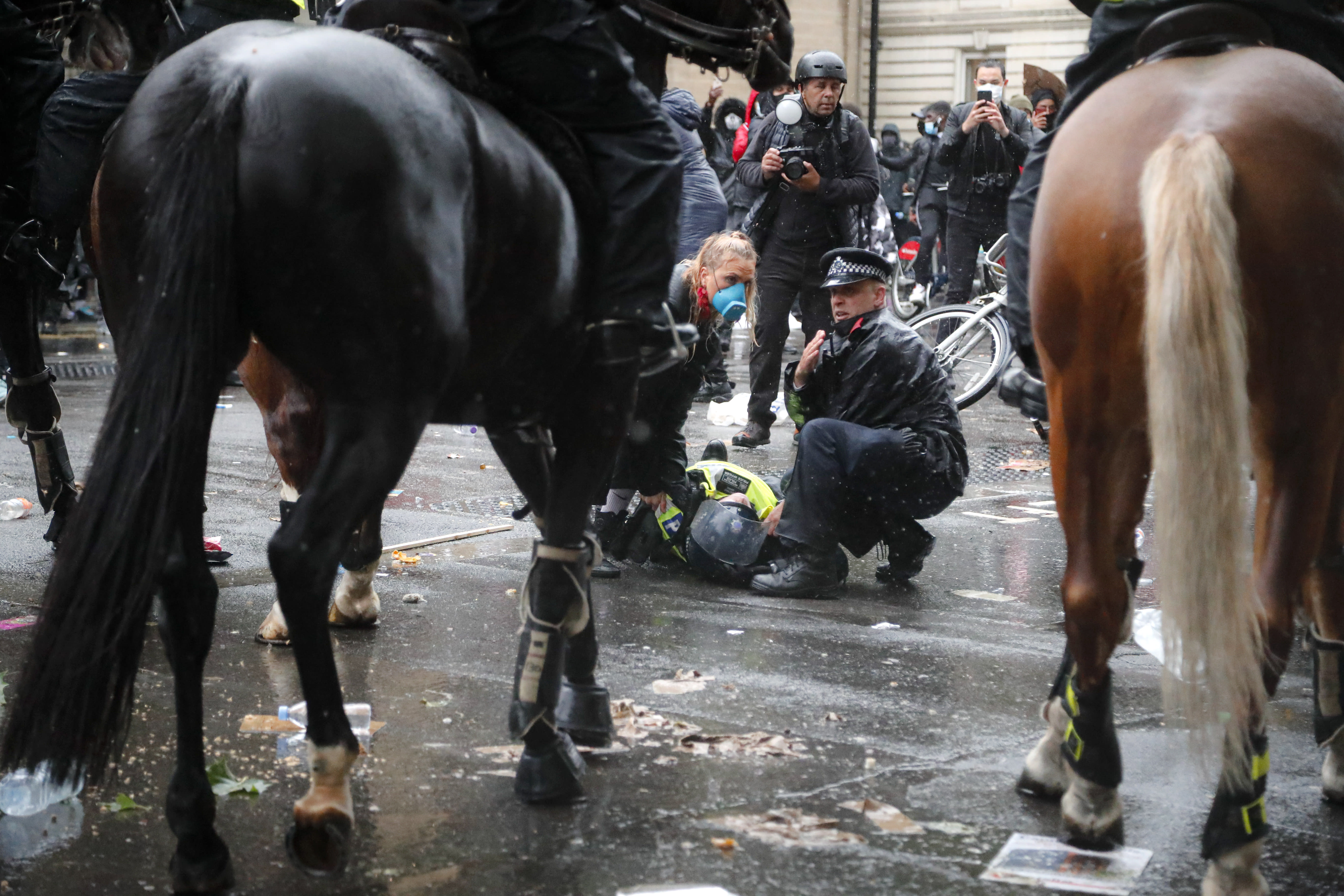 A colleague attends to a police officer who was injured when falling of a horse during scuffles with demonstrators at Downing Street during a Black Lives Matter march in London, Saturday, June 6, 2020, as people protest against the killing of George Floyd by police officers in Minneapolis, USA. Floyd, a black man, died after he was restrained by Minneapolis police while in custody on May 25 in Minnesota. (AP Photo/Frank Augstein)
