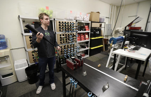 In this Feb. 8, 2018, photo, Kyle Hodge, product engineer for Axe Bat, holds a bat in the company's research lab in Renton, Wash. Axe Bat is trying to revolutionize baseball with a simple concept -- a baseball bat handle that is shaped like the handle of an axe. In the lab, the company uses scientific equipment and sensors to measure everything from the inertia of bat swings, the exit speed of baseballs hit by their bats, and the exact center of mass of each bat. (AP Photo/Ted S. Warren)