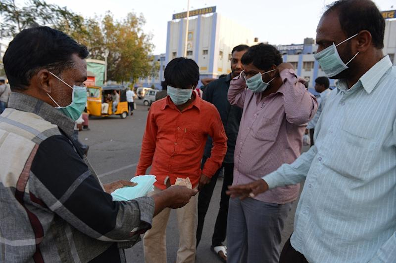 An Indian vendor (L) sells face masks for swine flu prevention outside a railway station in Secunderabad, India, on January 27, 2015 (AFP Photo/Noah Seelam)