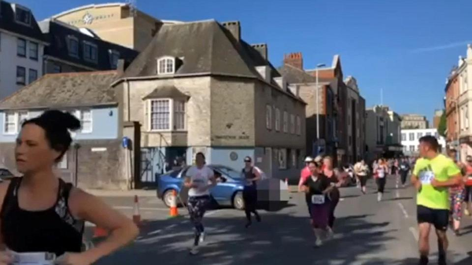 The car pulls out in front of runners (Picture: SWNS)