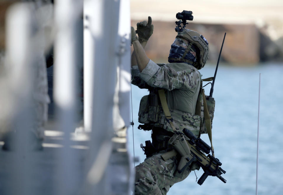 A special forces operator climbs on the side of a ship during a joint U.S.-Cyprus military drill at Limassol port on Friday, Sept. 10, 2021. Cyprus' Defense Minister Charalambos Petrides said the U.S. and Cyprus are on the same strategic path to ensure security and stability in a turbulent region and that continued close cooperation between the special forces of both countries aim to counter threats from potential terrorist acts. (AP Photo/Philippos Christou)