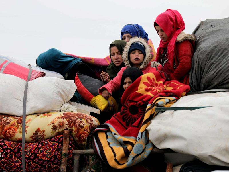 Internally displaced Syrians from western Aleppo countryside, ride on a vehicle with belongings in Hazano near Idlib, Syria, February 11, 2020: Reuters