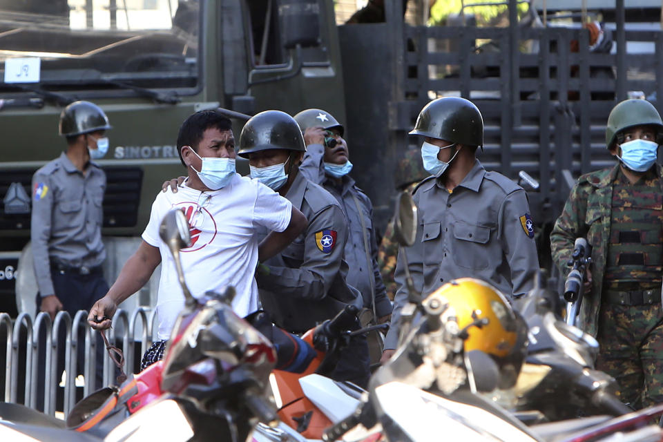 FILE - In this Feb. 15, 2021, file photo, a man is held by police during a crackdown on anti-coup protesters holding a rally in front of the Myanmar Economic Bank in Mandalay, Myanmar. One hundred days since their takeover, Myanmar's ruling generals maintain just the pretense of control over the country. There are fears the military takeover is turning Myanmar into a failed state. (AP Photo, File)