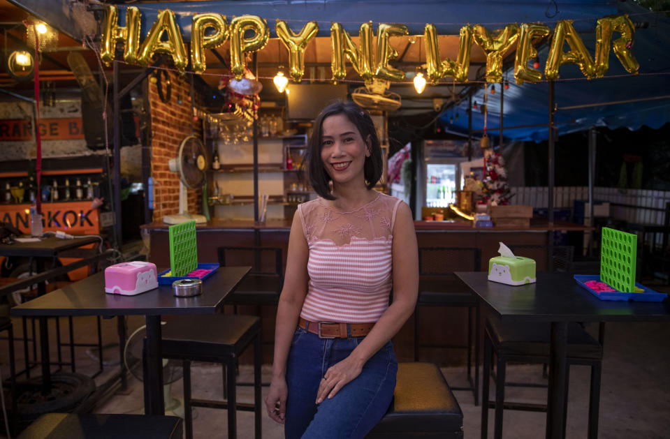 A hostess poses for a photo as she waits for customers at a bar in Bangkok, Thailand, Wednesday, Dec. 30, 2020. Officials in the Thai capital have announced new restrictions, including the closure of some entertainment facilities during the New Year's holiday, as infections continued to rise following a recent coronavirus outbreak. (AP Photo/Gemunu Amarasinghe)